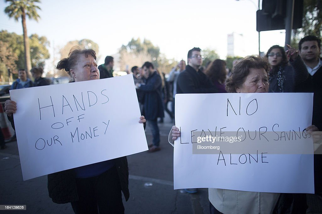 Demonstrators hold banners reading 'Hands off our money' and 'No, Leave our savings alone' during a protest outside the parliament against bank deposit tax plans in Nicosia, Cyprus, on Tuesday, March 19, 2013. Euro-area finance ministers told Cyprus to raise 5.8 billion euros ($7.5 billion) from bank depositors to unlock emergency loans, maintaining the revenue target while suggesting sparing small-scale savers. Photographer: Simon Dawson/Bloomberg via Getty Images