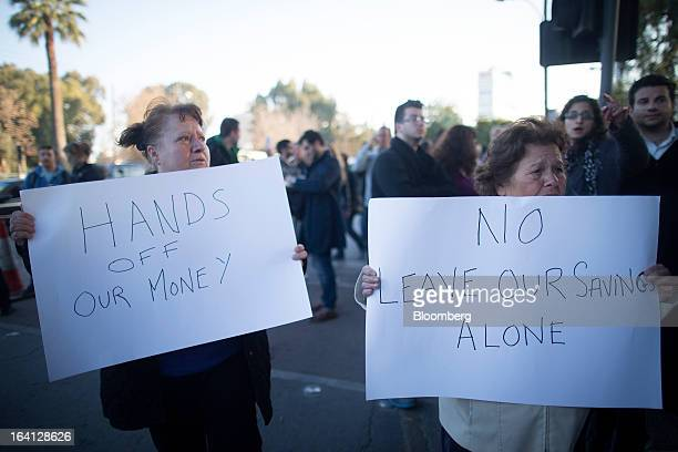 Demonstrators hold banners reading 'Hands off our money' and 'No Leave our savings alone' during a protest outside the parliament against bank...