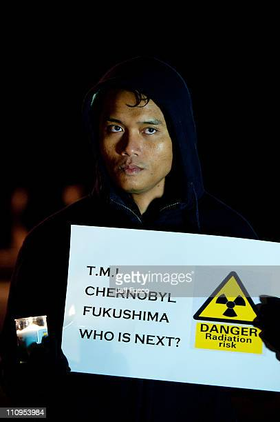 Demonstrators hold candles and signs at the 32nd annual vigil in remembrance of the disaster at the Three Mile Island Nuclear Plant March 28 2011 in...