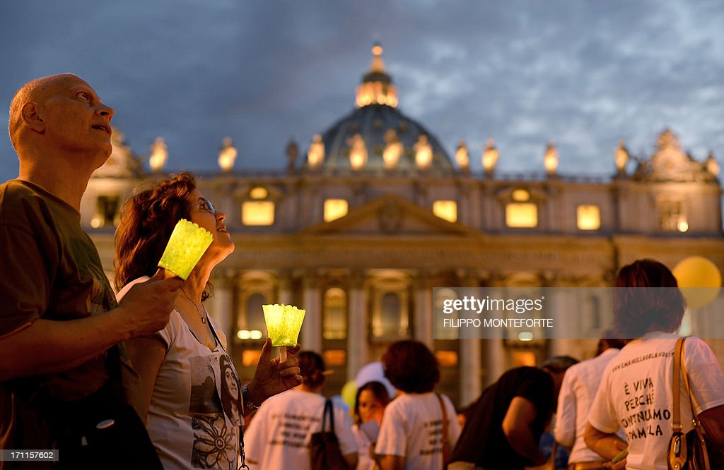 Demonstrators hold candles during a commemoration of the 30th anniversary of Emanuela Orlandi disappearance in St Peter's Square at the Vatican on June 22 2013. Fifteen-year-old Emanuela Orlandi, the daughter of a Vatican messenger who lived with his family in Vatican City, disappeared June 22, 1983 when she went to a music lesson. The still unsolved Orlandi saw over the years a number of theories regarding the motives for the crime from claimes that the kidnapping was done by extremist Muslim terrorists to demand the release of Mehmet Ali Agca from prison after he shot pope John Paul II to latest exorcist Gabriele Amorth claiming that she was kidnapped by a member of the Vatican police for sex parties, and then murdered. AFP PHOTO/ Filippo MONTEFORTE