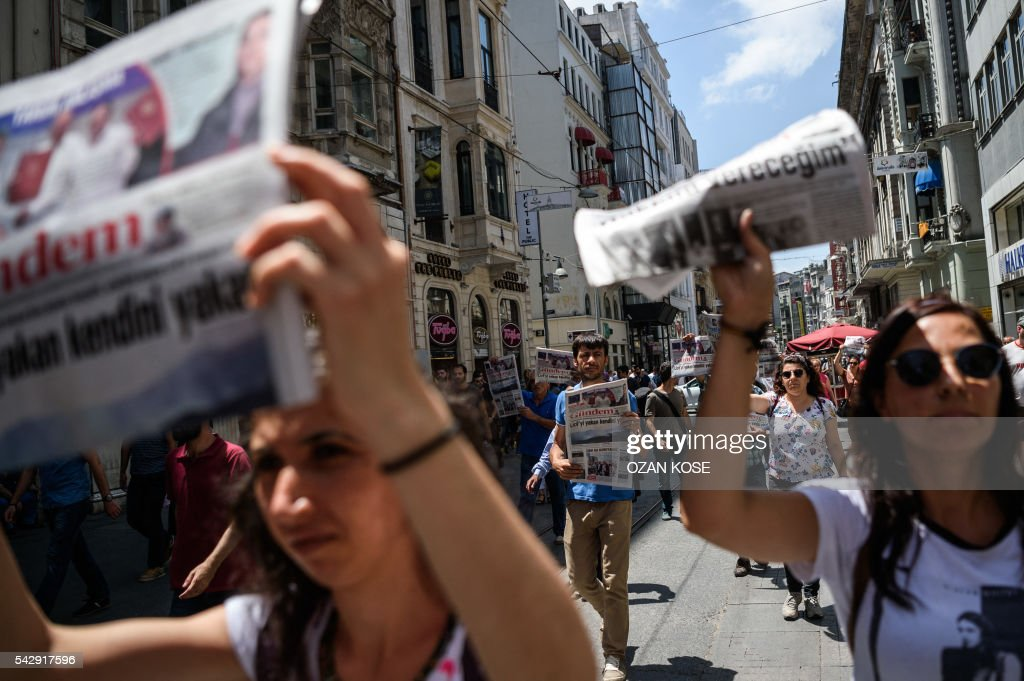 Demonstrators hold copies of pro-Kurdish newspaper 'Ozgur Gundem' as they a protest against the arrest of three prominent activists for press freedom on June 25, 2016 in Istanbul. Pro-Kurdish Turkish daily Ozgur Gundem has for weeks invited guest editors to take control of the newspaper, in a show of solidarity at a time when the government of President Recep Tayyip Erdogan is under fire for eroding press freedoms. The head of media rights watchdog Reporters Without Borders (RSF) on June 24 called for the release of the group's Turkey representative and two other activists held on 'terror propaganda' charges as he led a protest outside their prison in Istanbul. / AFP / OZAN