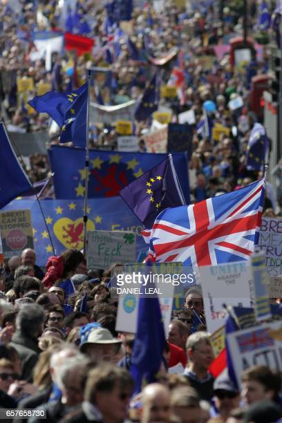 Demonstrators hold EU and Union flags as during an anti Brexit proEuropean Union march in London on March 25 ahead of the British government's...