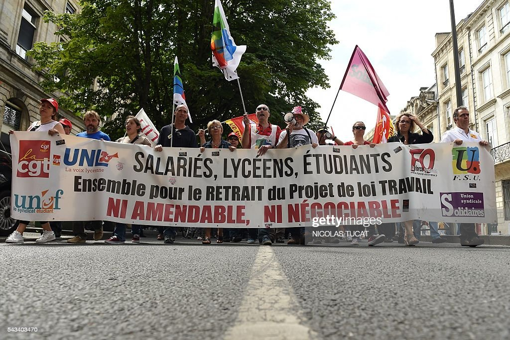 Demonstrators hold flags and a banner reading 'Workers, high school pupils, students, together against the labour law reform' during a demonstration against proposed labour law reforms in Bordeaux on June 28, 2016. Unions have called repeated strikes and marches against controversial labour reforms, forced through by the government of Socialist President Francois Hollande. / AFP / NICOLAS