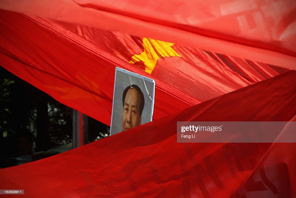 Demonstrators hold flags and a portrait of Chairman Mao during an antiJapanese protest over the disputed Diaoyu Islands known as the Senkaku Islands...