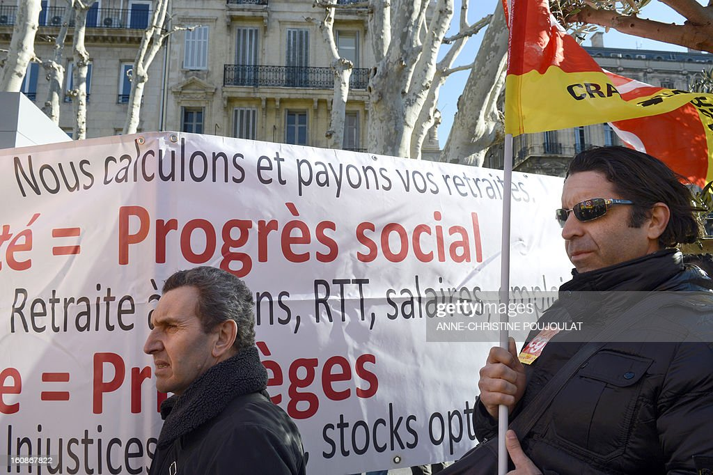 Demonstrators hold flags and banners in Marseille, on February 7, 2013, as they demonstrate during a nationwide protest of French welfare services workers to denounce the job cut program and the working conditions.