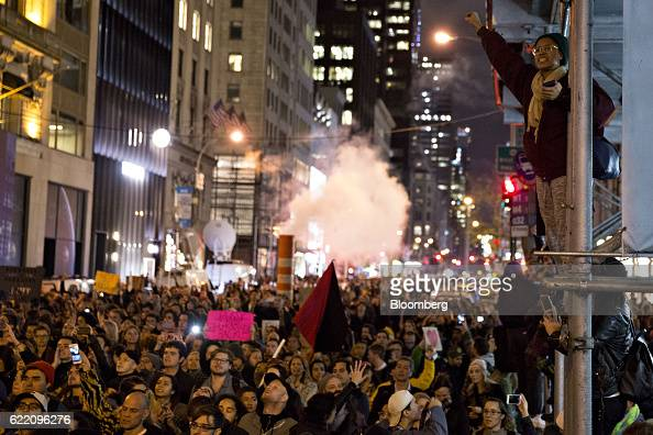 Demonstrators hold flags and signs as they gather outside Trump Tower during a rally against US Presidentelect Donald Trump in New York US on...