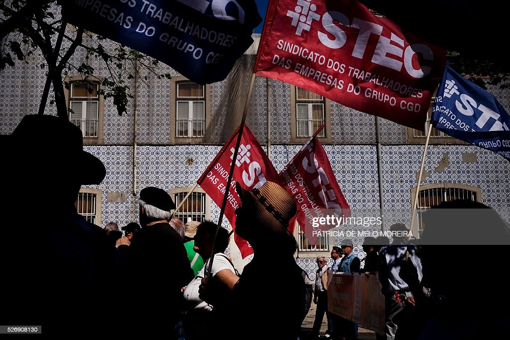 Demonstrators hold flags during the traditional May Day rally in Lisbon on May 1, 2016. Thousands of people demonstrated today in Lisbon and Portugal's main cities against the government's austerity measures. / AFP / PATRICIA
