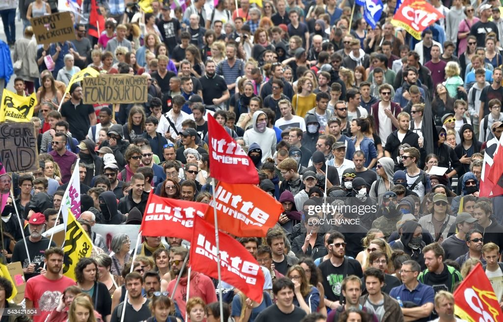 Demonstrators hold flags of political party 'Lutte Ouvriere' (Workers' Struggle) during a protest against controversial labour reforms, on June 28, 2016 in Nantes, western France. People took to the streets in France on June 28 in the latest protest march in a marathon campaign against the French Socialist government's job market reforms. Last month the government used a constitutional manoeuvre to push the bill through the lower house without a vote in the face of opposition from Socialist backbenchers. / AFP / LOIC