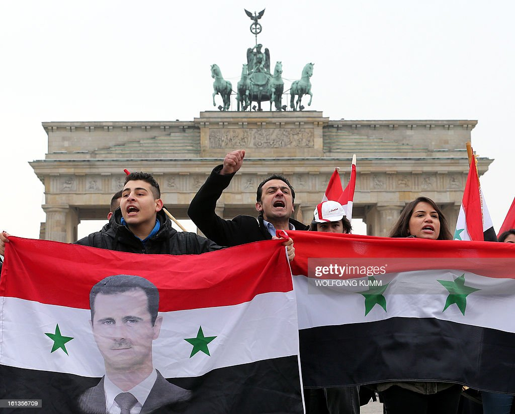 Demonstrators hold flags of Syria and a portrait of Syrian President Bashar al-Assad as they rally in front of Berlin's landmark the Brandenburg Gate to support Assad's regime on February 10, 2013 in Berlin. President Bashar al-Assad reshuffled his cabinet Saturday (February 9, 2013) as regime warplanes raided rebel areas in a bid to end the stalemate in Syria's deadly civil war and hopes for a political solution appeared to founder.