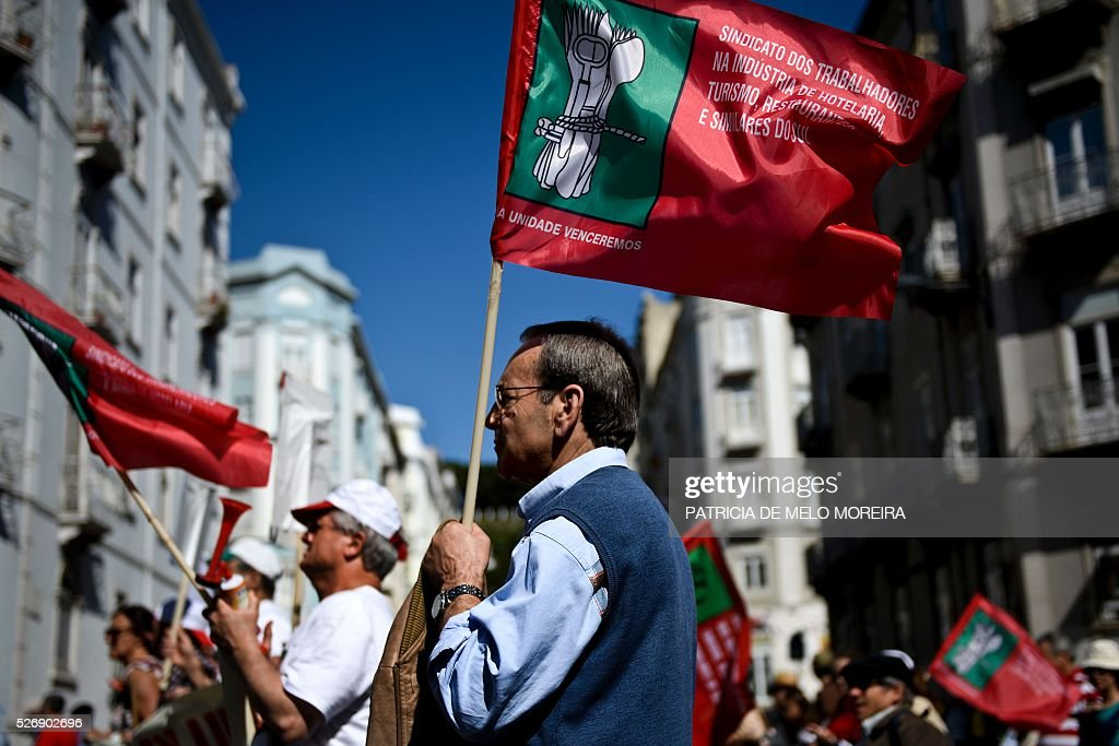 Demonstrators hold flags uring the traditional May Day rally in Lisbon on May 1, 2016. Thousands of people demonstrated today in Lisbon and Portugal's main cities against the government's austerity measures. / AFP / PATRICIA