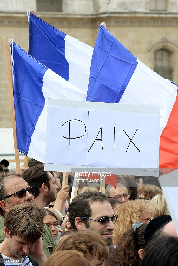 Demonstrators hold French national flags and a sign reading 'Peace' on August 3, 2014 in front of the Saint-Germain L'Auxerrois church in Paris as they take part in a demonstration originally called by a student on Facebook, and gathering Jews and Moslems to advocate peace and fraternity in the context of the Israeli offensive in Gaza. AFP PHOTO / PIERRE ANDRIEU