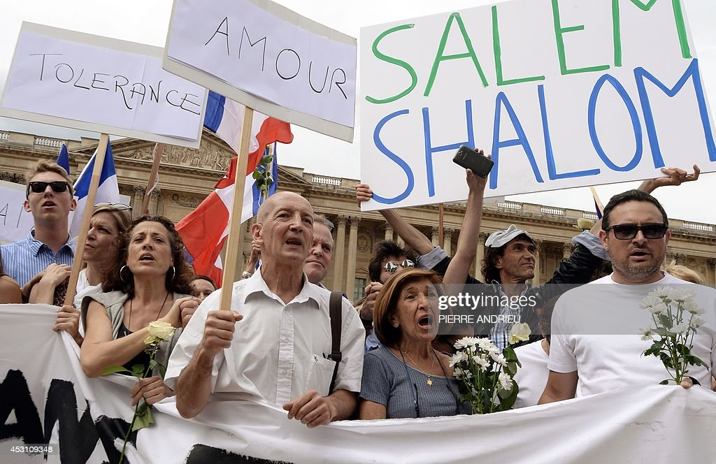 Demonstrators hold French national flags and boards reading messages of peace on August 3, 2014 in front of the Saint-Germain L'Auxerrois church in Paris as they take part in a demonstration originally called by a student on Facebook, and gathering Jews and Moslems to advocate peace and fraternity in the context of the Israeli offensive in Gaza. The signs read (from L) 'Tolerance', 'Love' and 'Salem Shalom'. AFP PHOTO / PIERRE ANDRIEU