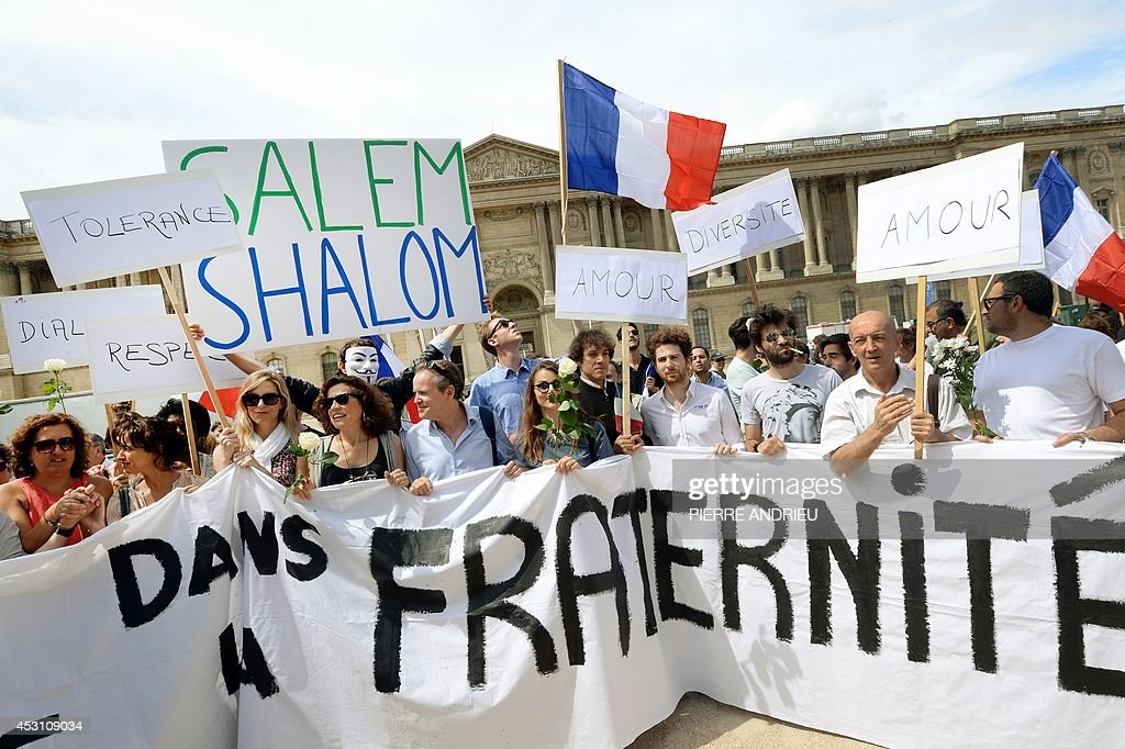 Demonstrators hold French national flags and boards showing messages of peace on August 3, 2014 in front of the Saint-Germain L'Auxerrois church in Paris as they take part in a demonstration originally called by a student on Facebook, and gathering Jews and Moslems to advocate peace and fraternity in the context of the Israeli offensive in Gaza. The banner reads 'All united in brotherhood'.