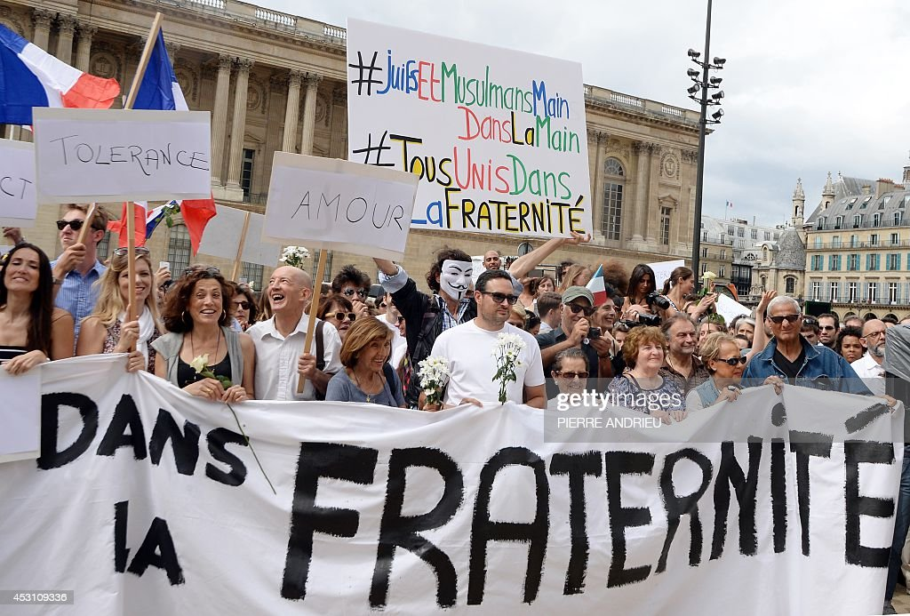 Demonstrators hold French national flags and boards showing messages of peace on August 3, 2014 in front of the Saint-Germain L'Auxerrois church in Paris as they take part in a demonstration originally called by a student on Facebook, and gathering Jews and Moslems to advocate peace and fraternity in the context of the Israeli offensive in Gaza. The banners read 'In brotherhood'(down) and '#Jews and Moslems hand in hand #all united in brotherhood' (top).