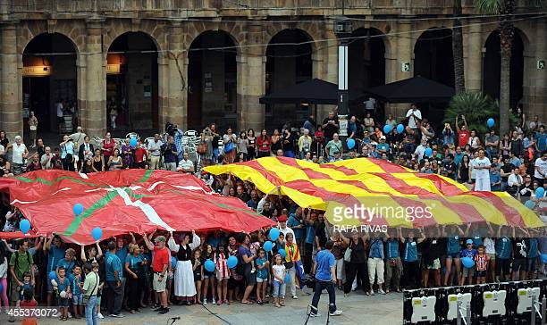 Demonstrators hold giant flags of the Basque Country and Catalonia during a demonstration called by Gure Esku Dago in support of a Catalan vote on...