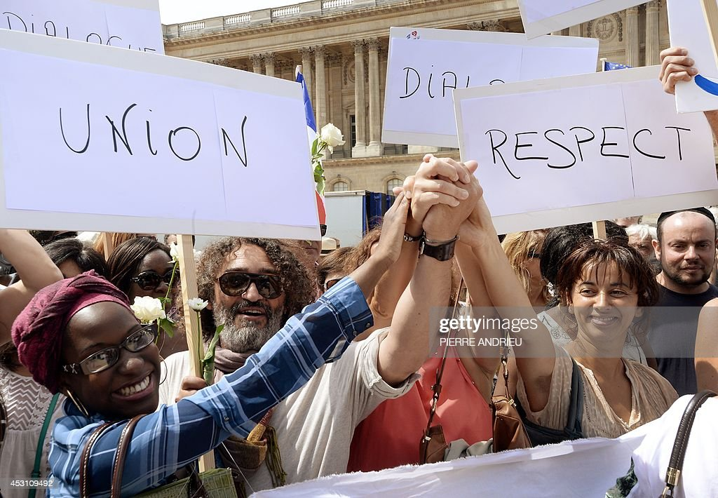 Demonstrators hold hands and sign reading messages of peace on August 3, 2014 in front of the Saint-Germain L'Auxerrois church in Paris as they take part in a demonstration originally called by a student on Facebook, and gathering Jews and Moslems to advocate peace and fraternity in the context of the Israeli offensive in Gaza. The signs read (from L) 'Union' and 'Respect'.
