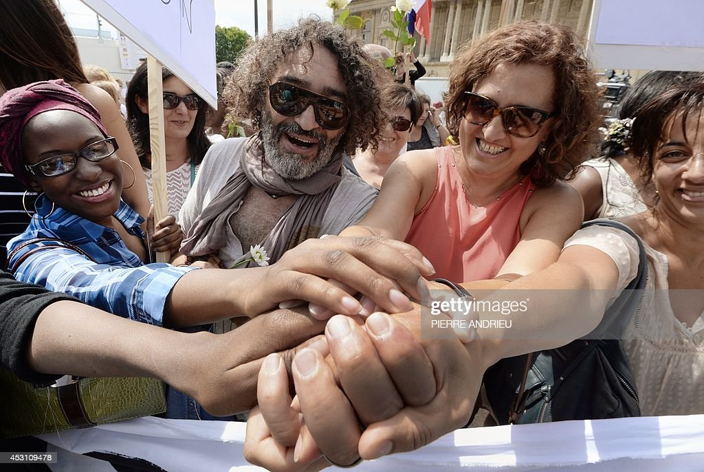 Demonstrators hold hands on August 3, 2014 in front of the Saint-Germain L'Auxerrois church in Paris as they take part in a demonstration originally called by a student on Facebook, and gathering Jews and Moslems to advocate peace and fraternity in the context of the Israeli offensive in Gaza.