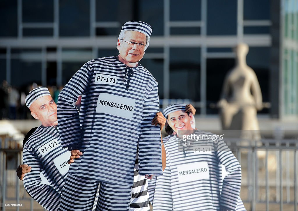 Demonstrators hold images of Brazilian politicians Jose Dirceu and Joao Paulo Cunha and publicist Marcos Valerio some of the defendants in the trial...