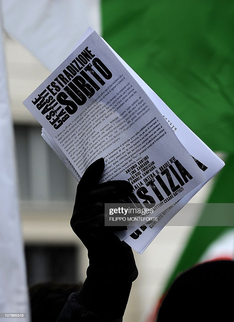 Demonstrators hold leaflets reading 'Extradition now' in front of Brazil's embassy to protest Brazilian President Lula's refusal to extradite ex-militant Cesare Battisti on January 4, 2011 at Piazza Navona in Rome. President Luiz Inacio Lula da Silva's refusal on December 31 to extradite Battisti, a member of the Armed Proletariat for Communism (PAC), a radical and armed left-wing group that killed several people in the 1970s, sparked a wave of indignation across Italy. Battisti has been found guilty of the group's 1978-1979 murders of a prison guard, a special investigator of terrorist organisations, a butcher and a jeweller, and in 1993 was sentenced in his absence to life in prison.