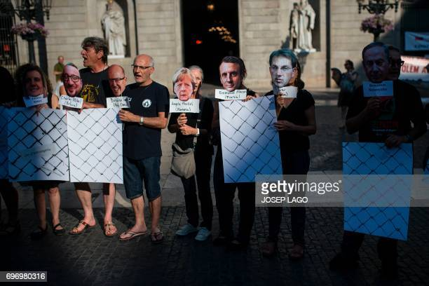 Demonstrators hold masks wiht the faces of different political leaders during a prorefugees concentration called by more than one hundred...