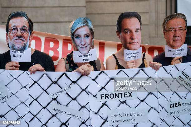 Demonstrators hold masks with faces of Spanish Prime Minister Mariano Rajoy President of the French farright party Front National Marine Le Pen Head...