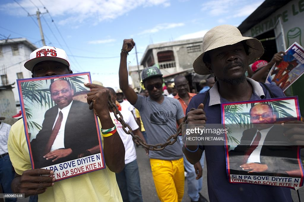Demonstrators hold pictures of former Haitian President Jean Bertrand Aristide during a march in the center of Port-au-Prince against the government of Haitian President Michel Martelly on January 1, 2015, the date of which also marks Independence Day celebrations in Haiti. Protesters marched through the streets calling for the resignation of the Haitian leader. Police dispersed protesters with tear gas. AFP PHOTO/Hector RETAMAL