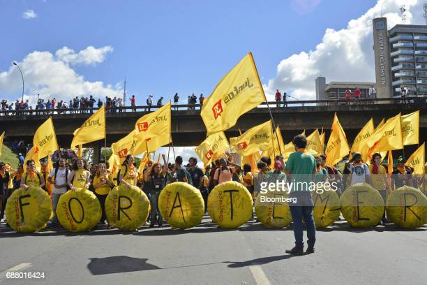 Demonstrators hold placards and flags during protests outside of the National Congress demanding the resignation of Brazilian President Michel Temer...