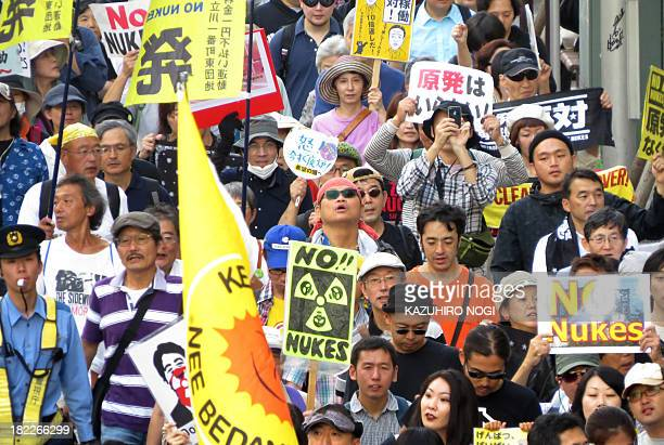 Demonstrators hold placards and shout slogans during an antinuclear power rally in Tokyo on September 29 2013 Some 700 people staged a rally...
