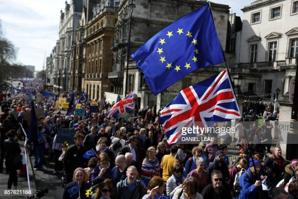 Demonstrators hold placards and wave EU and Union flags during an anti Brexit proEuropean Union march in London on March 25 ahead of the British...