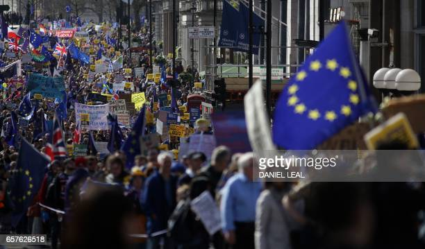 Demonstrators hold placards and wave EU flags during an anti Brexit proEuropean Union march in London on March 25 ahead of the British government's...