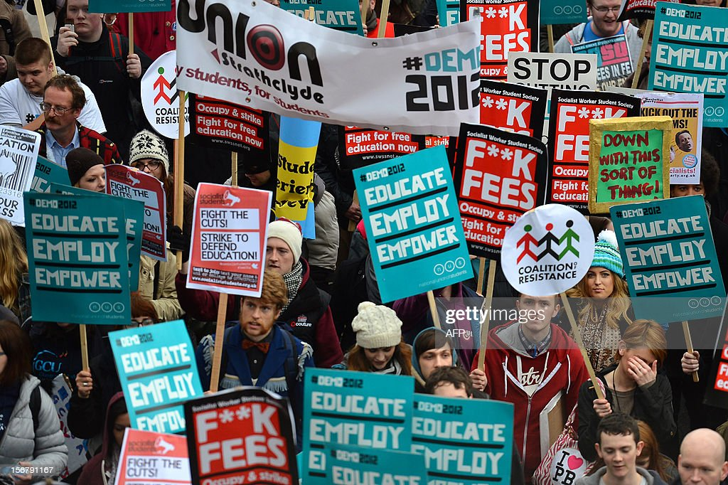 Demonstrators hold placards as they gather before the start of a student rally in central London on November 21, 2012 against sharp rises in university tuition fees, funding cuts and high youth unemployment.