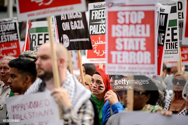 Demonstrators hold placards as they gather near the Israeli embassy in central London on August 1 calling for an end to violence in the Gaza Strip...