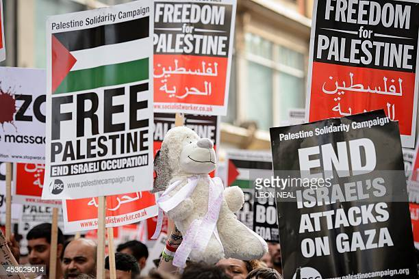 Demonstrators hold placards as they gather near the Israeli embassy in central London on August 1 calling for an end to Israel's military offensive...