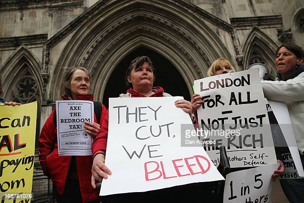 Demonstrators hold placards as they gather to protest against government changes to the welfare system and the proposed 'Bedroom Tax' outside the...