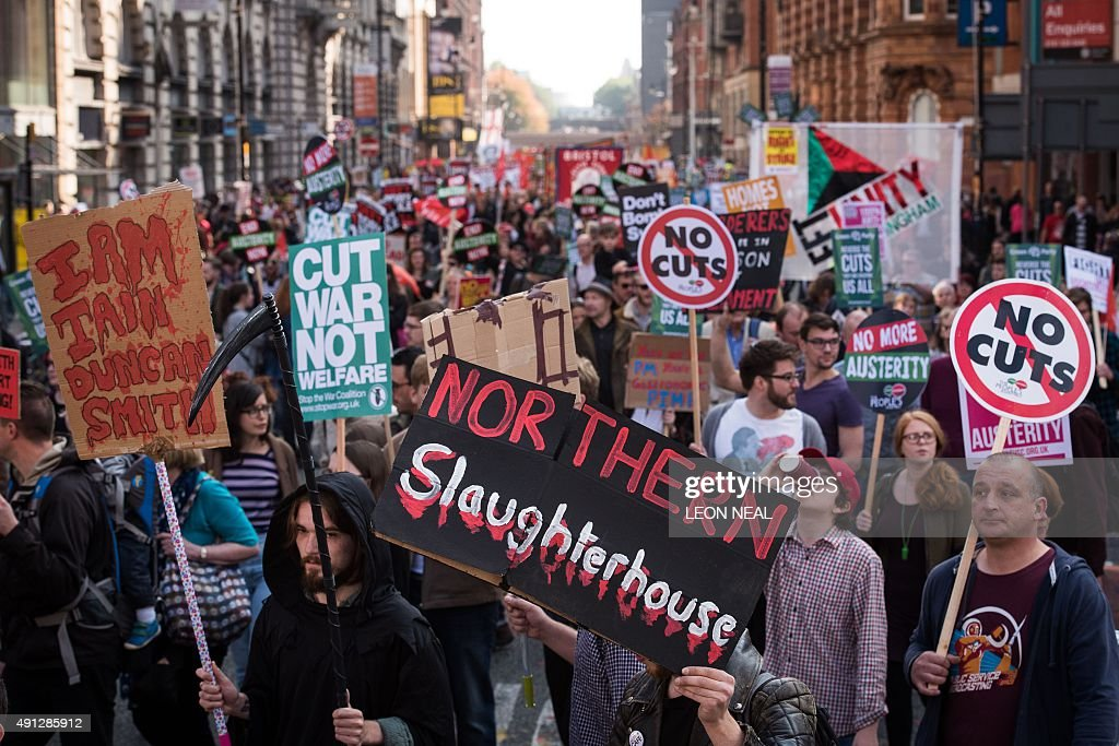 Demonstrators hold placards as they march through the streets of Manchester in protest against the British Conservative government on the first day...