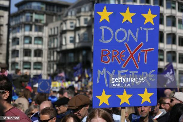 Demonstrators hold placards as they prepapre to participate in an anti Brexit proEuropean Union march in London on March 25 ahead of the British...