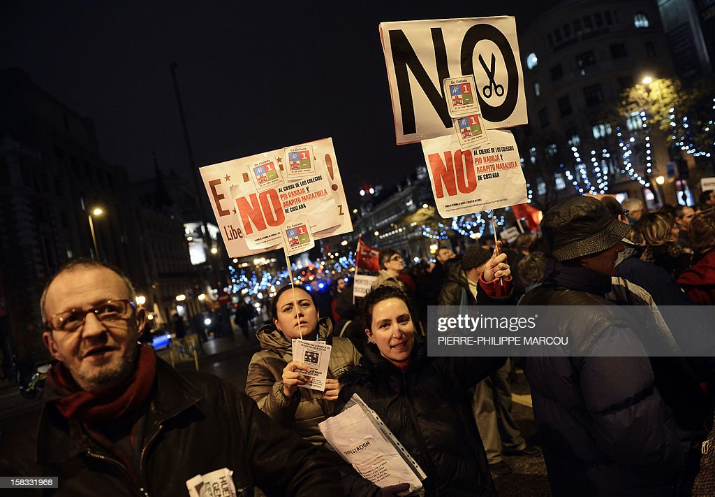 Demonstrators hold placards as they take part in a protest against government's austerity reforms and cuts in Madrid on December 13, 2012. Public spending on education has been cut by more than a billion euros this year compared with 2011, and public schools employed nearly 3,000 fewer teachers during the 2011-12 academic year, according to the education ministry.