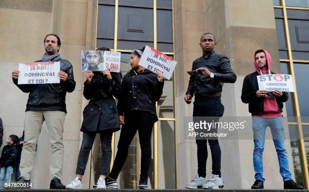 Demonstrators hold placards as they take part in a rally in front of The Eiffel Tower in Paris on September 16 to protest the situation of Rohingya...