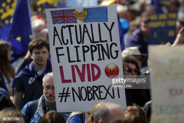 Demonstrators hold placards during an anti Brexit proEuropean Union march in London on March 25 ahead of the British government's planned triggering...