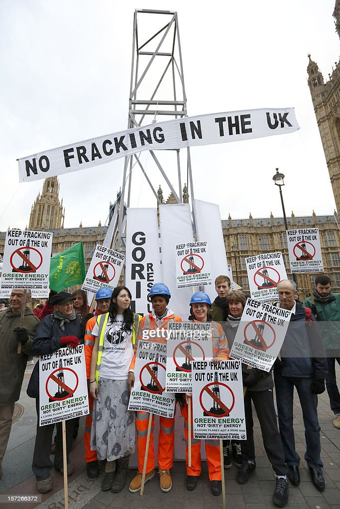 Demonstrators hold placards in front of their mock fracking rig in protest against hydraulic fracturing for shale gas outside the Houses of Parliament in London on December 1, 2012. The demonstration organised by various groups protested against any expansion into Britain of the pratcice of 'hydraulic fracturing' or 'fracking' for shale gas which the Campaign Against Climate Change group, one of the organisations involved in the action, characterises as 'risky' and 'destructive'.