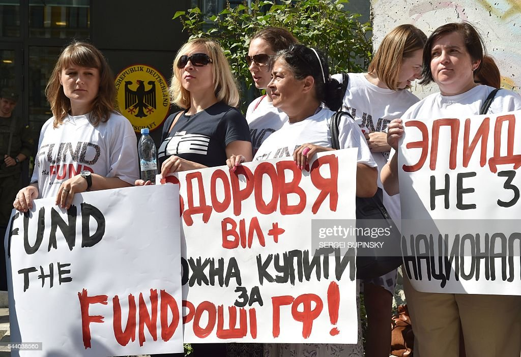 Demonstrators hold placards reading 'Epidemic does not know the nationality', 'Will stop AIDS and tuberculosis together', 'Human rescue by medication but not promises' in front of German embassy in Kiev on July 1, 2016 during a demonstration called by the Fund the Fund international organisation aimed at increasing donor countries funding for programs to fight HIV / AIDS and tuberculosis. / AFP / SERGEI