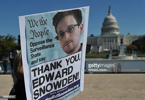 Demonstrators hold placards supporting former US intelligence analyst Edward Snowden during a protest against government surveillance on October 26...