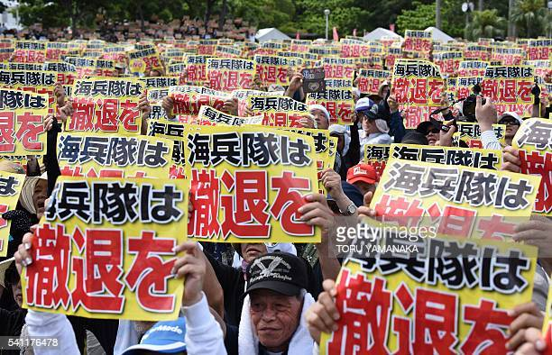 Demonstrators hold placards that read 'Withdraw Marine Corps' during a rally against the US military presence in Naha Okinawa prefecture on June 19...
