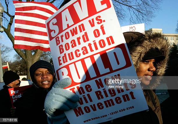 Demonstrators hold posters as they protest a challenge to current laws that mandate racial integration in schools to avoid the same segregation found...