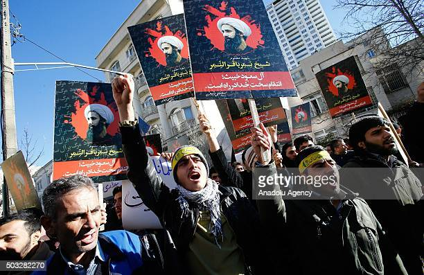 Demonstrators hold posters of Nimr Baqir alNimr and shout slogans during a protest rally outside the embassy of Saudi Arabia against the execution of...