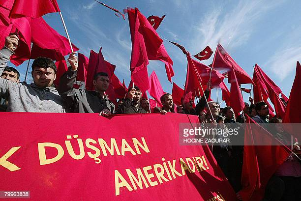 Demonstrators hold red flags and a banner reading 'The United States is the common ennemy' while staging a protest against a Turkish offensive to...