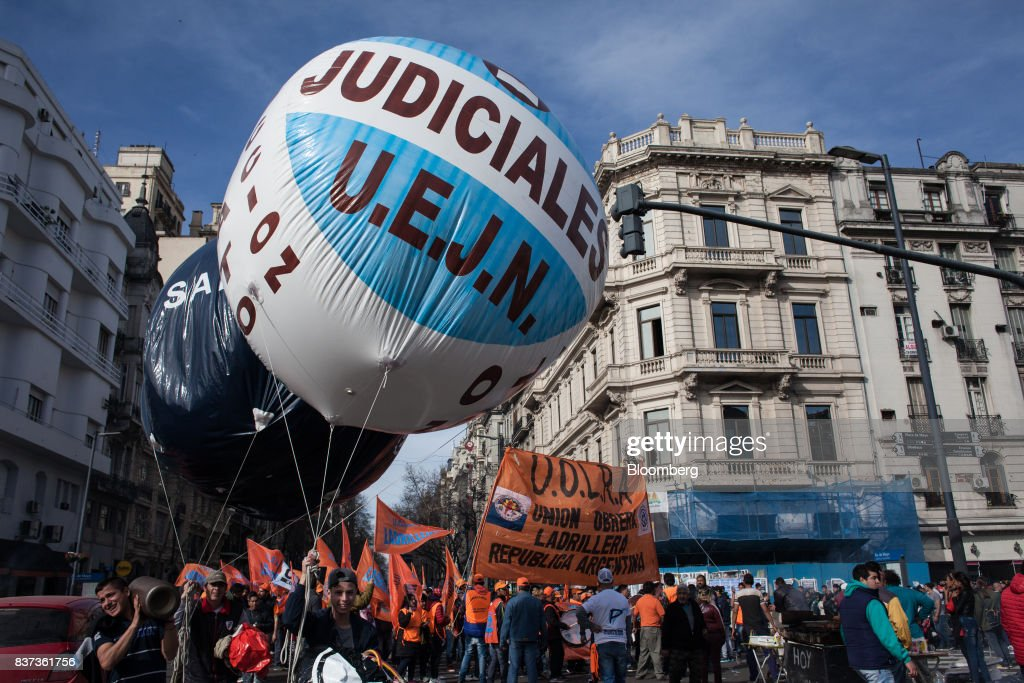 Demonstrators hold signs and a large balloon during a protest in Buenos Aires, Argentina, on Tuesday, Aug. 22, 2017. Union groups protested Argentinean President Mauricio Marcri's economic policies. Photographer: Erica Canepa/Bloomberg via Getty Images