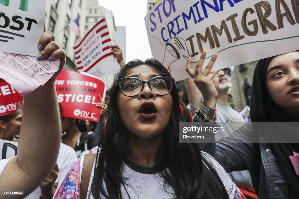 Demonstrators hold signs and chant during the 'Defend DACA & TPS' rally outside of Trump Tower in New York, U.S., on Tuesday, Aug. 15, 2017. A day after belatedly faulting white supremacists for deadly clashes in Virginia, President Donald Trump returned to his controversial position that there was 'blame on both sides' for the weekend violence, saying that liberal counter-protesters also bore responsibility. Photographer: Jeenah Moon/Bloomberg via Getty Images