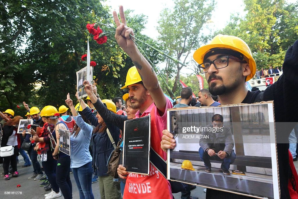 Demonstrators hold signs and gesture on May 31, 2016 in Ankara during a demonstration commemorating the third anniversary of the start of the Gezi Park protests. The Gezi Park protests which began in May 2013, were sparked by the heavy-handed eviction of demonstrators staging a sit-in protest against the redevelopment of the area and grew into often violent clashes with police as people demonstrated against much broader issues concerning perceived infringements of civil rights. / AFP / ADEM