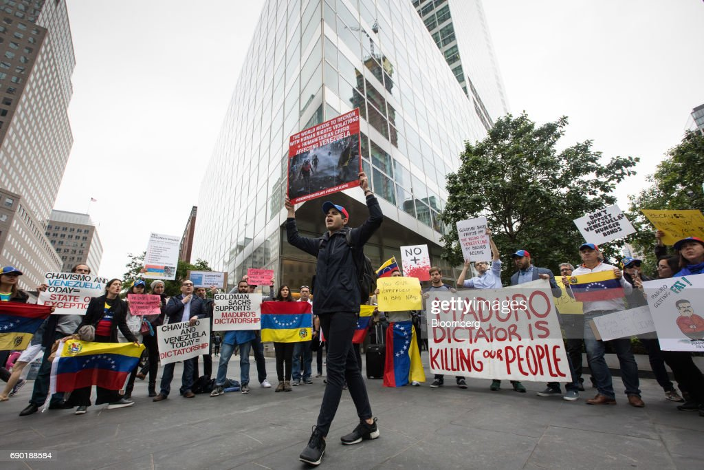 Demonstrators hold signs and Venezuelan flags during a protest outside of the Goldman Sachs Group Inc. headquarters in New York, U.S., on Tuesday, May 30, 2017. Goldman faces a probe by Venezuela's opposition leaders after buying bonds issued in 2014 by the state oil company, a purchase some lawmakers said bolsters President Nicolas Maduro as he grapples with accusations of human-rights violations. Photographer: Alexander F. Yuan/Bloomberg via Getty Images